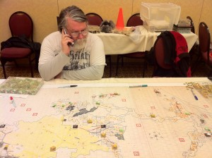 Andrew Nisbet surveys an Empire map and pieces being set up to play Tac 5 (March 2011 at the GameStorm convention in Vancouver, WA)